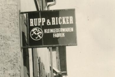 <h5>1962</h5><p>Firmenschild der Firma Rupp & Ricker in der Ludwigstrasse. Später wird die Marke Esquire auch Firmenname.</p>