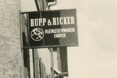 <h5>1962</h5><p>Company sign of Rupp & Ricker in the Ludwigstrasse. Lateron the brand Esquire becomes part of the company name.																																																																																					</p>