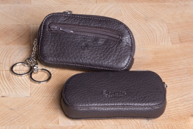 <h5>3961 09</h5><p>Key case in black and brown with 2 rings and a front zip pocket. Size: 11,5 x 6,5 cm</p>