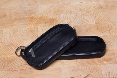 <h5>3965 45</h5><p>Key case with zip in black with 2 key chains and front zip compartment. Size: 12 x 6,5 cm</p>
